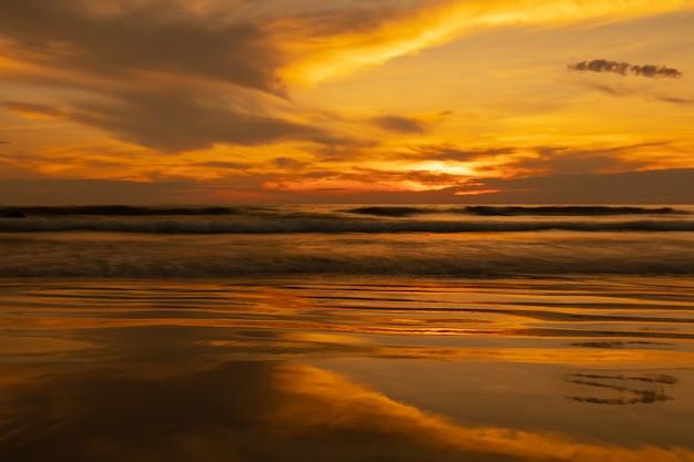 Ansicht eines goldenen himmels bei sonnenuntergang mit den wellen, die meer zusammenstoßen