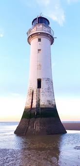 Ansicht eines leuchtturms liverpool bei sonnenuntergang, drucke des wasserspiegels auf der fassade, vereinigtes königreich