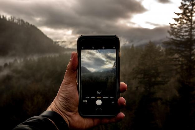 Ansicht eines mannes, der ein smartphone hält und ein foto einer schönen landschaft macht