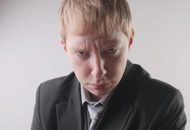 Ansicht eines mannes, der einen dunklen anzug mit einem wütenden gesichtsausdruck trägt - konzept: wütend