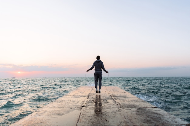 Ansicht in voller länge des jungen mannes in der sportkleidung, die mit springseil, training auf pier springt