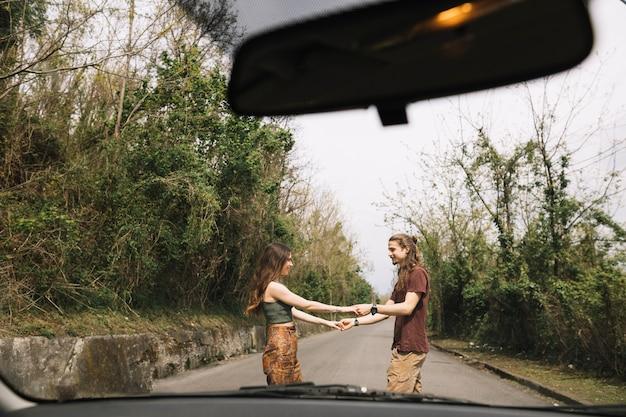 Ansicht vom auto der jungen paare in der mitte der straße