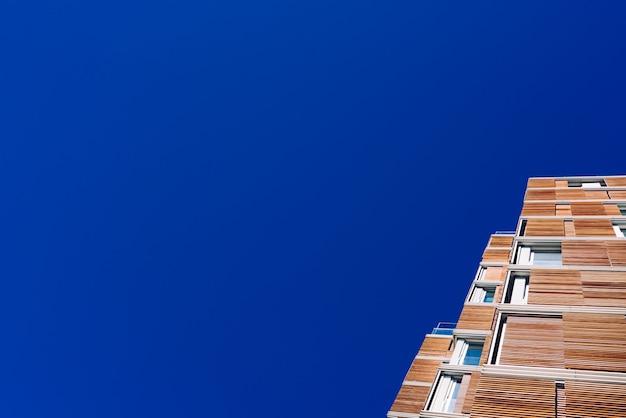Ansicht vom boden der fassade eines modernen gebäudes, das im ökologischen holz über sauberem blauem himmel gekleidet wird