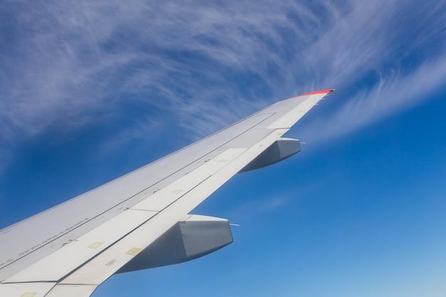 Ansicht vom flugzeugfenster mit blauem himmel und weißen wolken