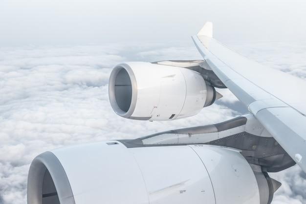 Ansicht vom flugzeugfenster und vom flügel, über flaumigen wolken, fliegen und reisendem konzept