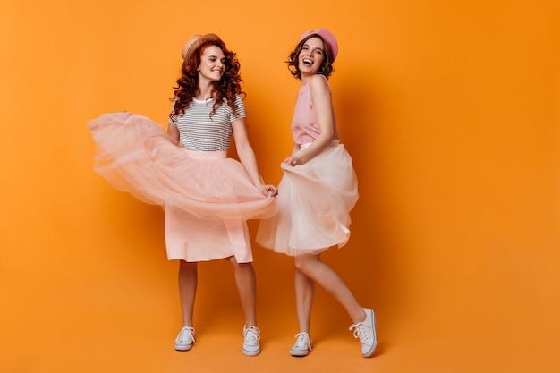 Ansicht von bezaubernden trendigen mädchen in voller länge. freundinnen tanzen auf gelbem hintergrund.