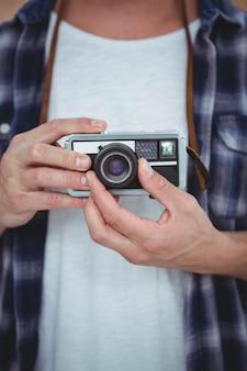 Ansicht von den männlichen händen, die eine retro- kamera halten