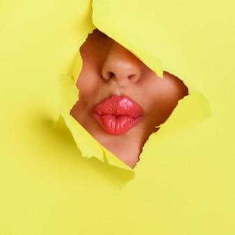 Ansicht von den schönen rosa lippen, die kuss durch loch im papierhintergrund geben.
