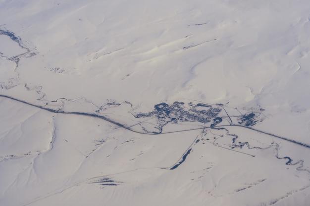 Ansicht von der höhe der flugzeuge auf dem dorf im schneebedeckten sibirien in russland