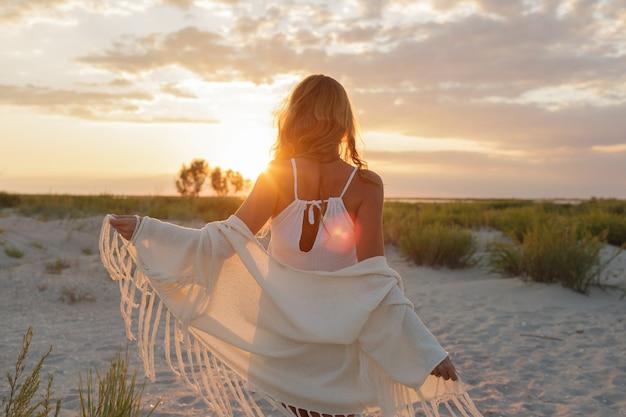Ansicht von der rückseite der anmutigen ingwerfrau, die erstaunlichen sonnenuntergang am strand genießt.