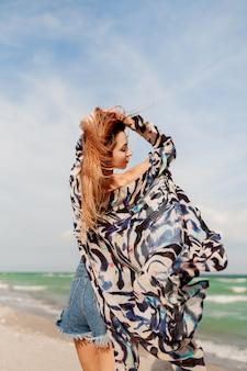 Ansicht von der rückseite des schlanken braunen rothaarigen mädchens im stilvollen tropischen outfit, das auf erstaunlichem strand nahe ozean aufwirft.