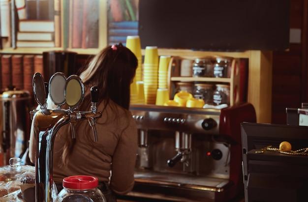 Ansicht von der rückseite des weiblichen barista, der kaffee in der professionellen kaffeemaschine zubereitet