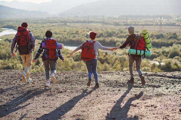 Ansicht von der rückseite von vier hipster-freunden mit reiserucksack händchen haltend