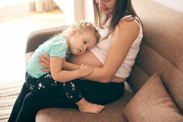 Ansicht von der seite des mädchens, das bauch der schwangeren mutter umarmt