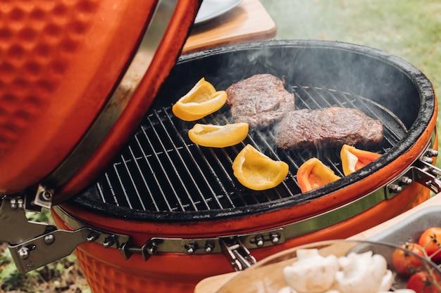 Ansicht von der seite des mannes steaks und gemüse auf grill kochend