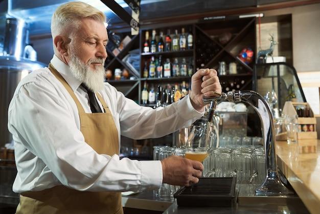 Ansicht von der seite des ruhigen mannes, der schürze im prozess des gießens von leichtem bier in glas vom bierhahn trägt. männlicher brauer, der an der fabrik und an der kneipe arbeitet. konzept der ale-produktion.