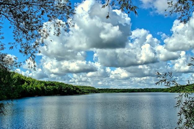 Ansicht von einem see, von wald und von blauem himmel mit weißen wolken