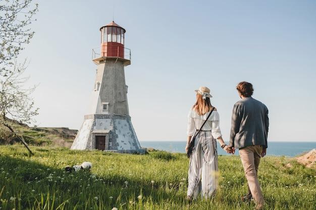 Ansicht von hinten auf hipster-indie-stil des jungen paares in der liebe, die in der landschaft geht, händchen haltend, leuchtturm auf hintergrund, warmer sommertag, sonniges, böhmisches outfit, hut
