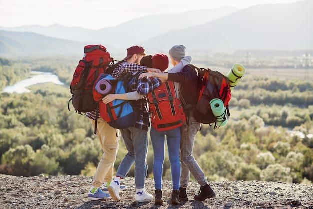 Ansicht von hinten von vier hipsterfreunden reisenden, die hände halten, die auf der spitze des berges stehen