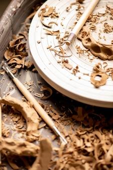 Ansicht von hölzernen handwerkzeugen und rad für die herstellung von keramik mit lehmspänen am arbeitsplatz in der nähe