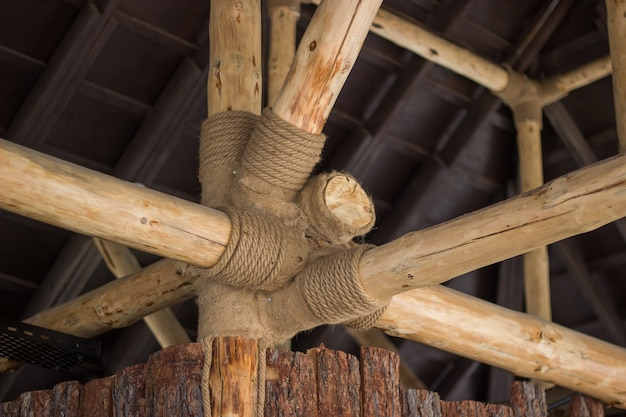 Ansicht von holzbalkensparren bei der installation des daches auf dem bau des mit bindfäden verzierten hauses.