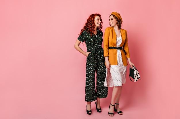 Ansicht von jungen frauen im vintage-outfit in voller länge. studioaufnahme von fröhlichen freunden, die auf rosa hintergrund sprechen.