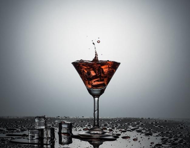 Ansicht von martini-glas, das spritzen durch eiswürfel mit rotem wasser erhält