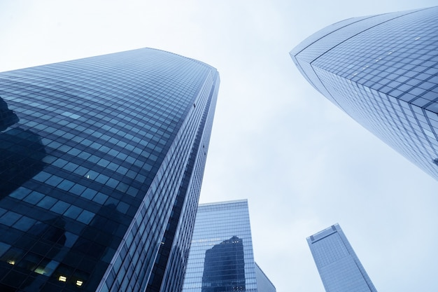 Ansicht von modernen gebäuden aus glasmaterial blau gefärbt. hohe häuser und blauer himmel. hochhäuser, die sich bis zum himmel erstrecken.