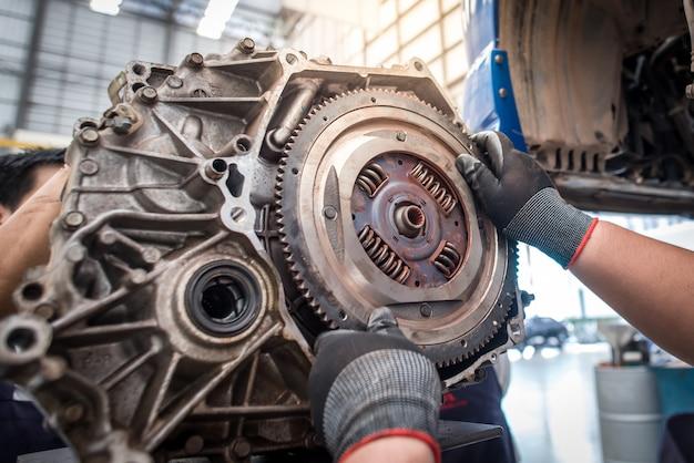 Ansicht von motorteilen, motorteilen und schwungrad- oder schwungradautos handautomechanikerarbeiten autoreparaturservice