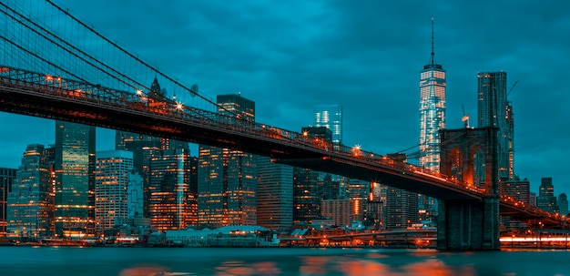 Ansicht von new york city manhattan midtown in der abenddämmerung mit brooklyn bridge.