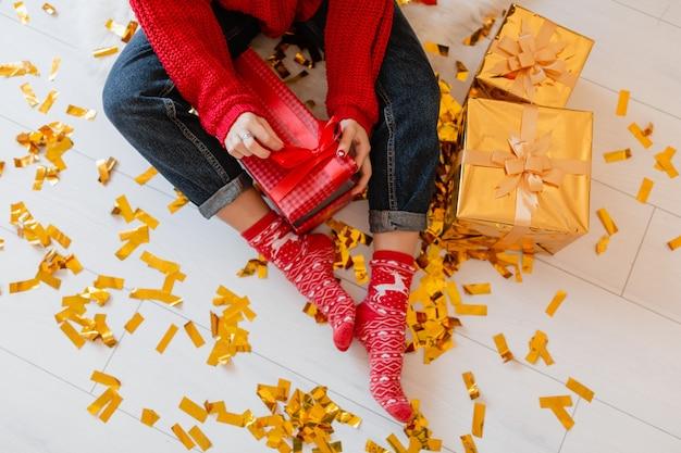 Ansicht von oben auf frau in den roten socken, die zu weihnachten zu hause auf goldenen konfetti sitzen, die ausstellungsstücke und geschenkboxen auspacken