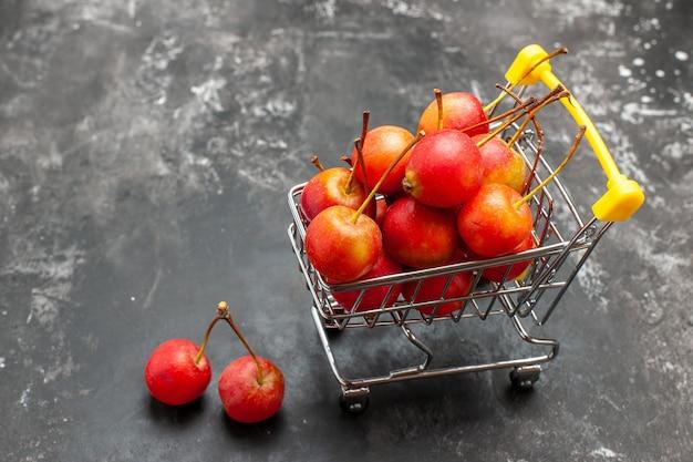 Ansicht von oben auf rote kirschen innerhalb und außerhalb der mini-einkaufstabelle