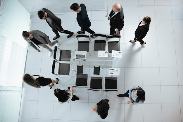 Ansicht von oben. eine gruppe von geschäftsleuten geht in den konferenzraum