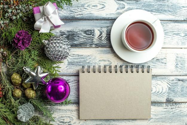 Ansicht von oben eine tasse tee notizblock kleines geschenk tannenbaum zweige weihnachtsspielzeug auf holzuntergrund