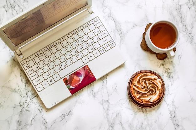 Ansicht von oben genanntem auf frauenhänden auf weißem marmor halten eine tasse tee und einen kuchen nahe weißem laptop.
