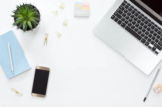 Ansicht von oben genanntem der weißen schreibtischtabelle mit laptop, notizbuch, handy, grüner blume und zubehör, ebenenlage. draufsicht mit kopienraum.