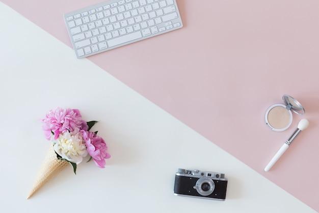 Ansicht von oben genanntem des mode bloggerarbeitsplatzes mit weißer tastatur, intelligentem telefon, weiblichem zusatz, kosmetikprodukten, kamera auf pastellrosa und weißem hintergrund. flache lage, beauty-business-konzept