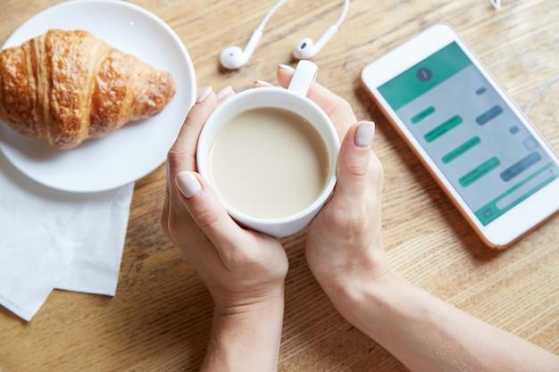 Ansicht von oben genanntem von den weiblichen händen, die einen tasse kaffee halten