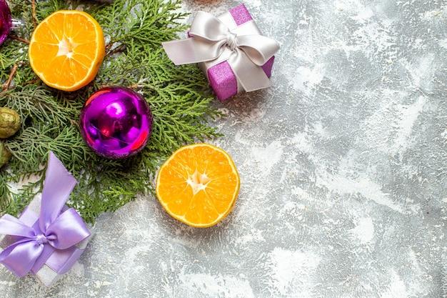 Ansicht von oben geschnitten orangen kiefer zweige weihnachtsbaum spielzeug kleine geschenke auf grauem hintergrund