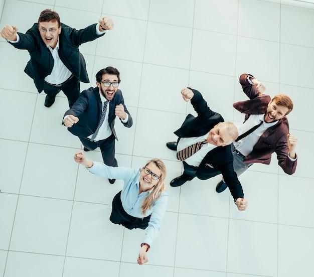Ansicht von oben. gruppe glücklicher menschen, die ihren erfolg zeigen. das erfolgskonzept.