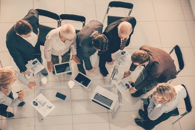 Ansicht von oben. gruppe von mitarbeitern, die finanzstatistiken diskutieren.