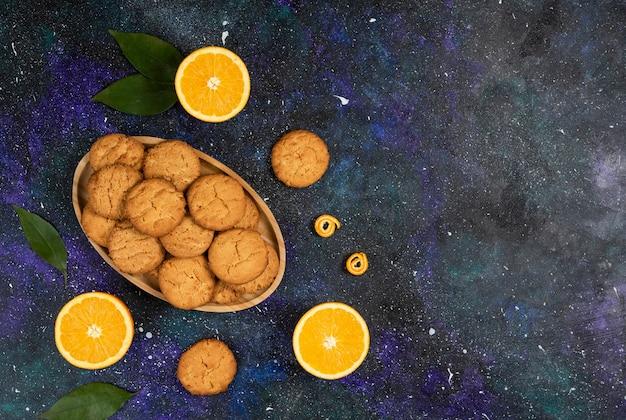 Ansicht von oben. haufen hausgemachter frischer kekse und kekse mit orange über der raumoberfläche.