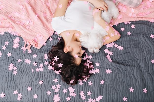 Ansicht von oben hübsche frau im pyjama, die mit kleinem hund auf bett mit rosa decke kühlt. genießen sie ihr zuhause und entspannen sie sich in rosa lametta. wochenenden genießen, fröhliche stimmung, mit geschlossenen augen lächeln