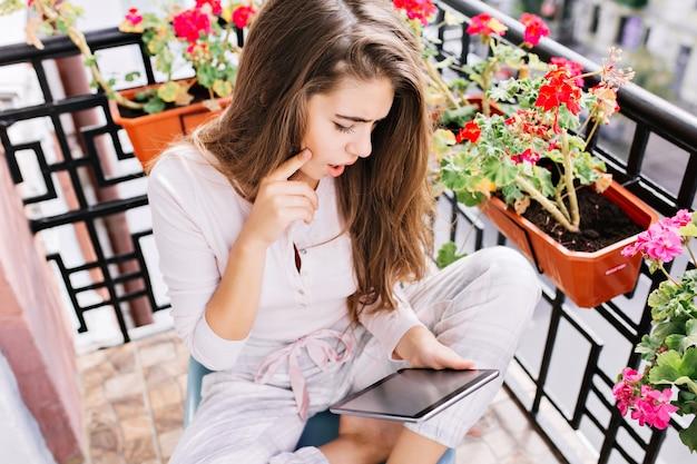 Ansicht von oben hübsches junges mädchen mit langen haaren im pyjama auf balkon am morgen. sie liest auf dem tablet und sieht erstaunt aus.