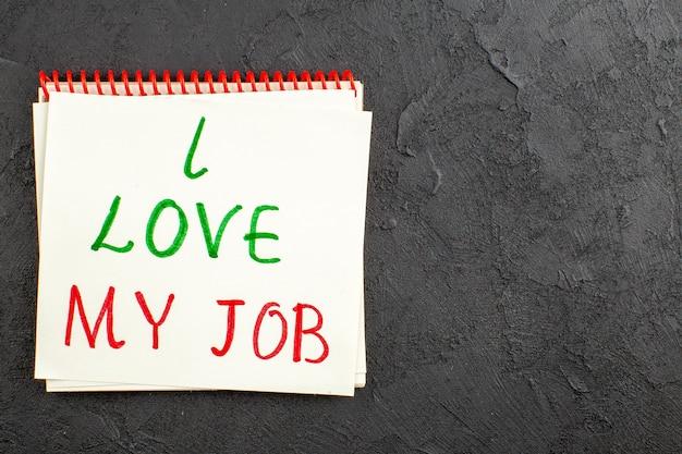 Ansicht von oben ich liebe meinen job auf papier auf notizblock auf schwarzem tisch freien platz geschrieben