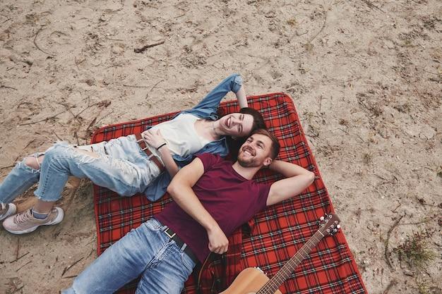Ansicht von oben. junges paar hat picknick am strand. auf der roten decke liegend.