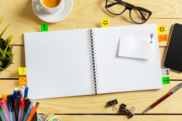 Ansicht von oben. kaffeetasse mit kaffee. stift auf leeres notizbuch setzen.