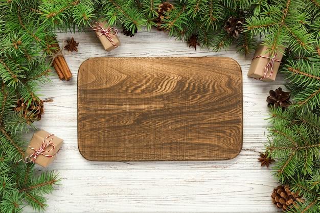 Ansicht von oben. leere hölzerne rechteckige platte auf hölzerner weihnachtsoberfläche.