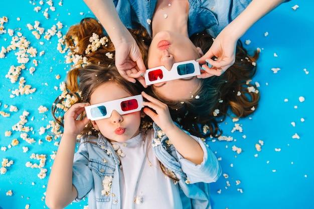 Ansicht von oben lustige mutter und tochter, die auf boden legen und spaß haben, kamera in popcorn lokalisiert auf blauem hintergrund. modische familie in jeanskleidung, 3d-brille tragend, glück ausdrücken