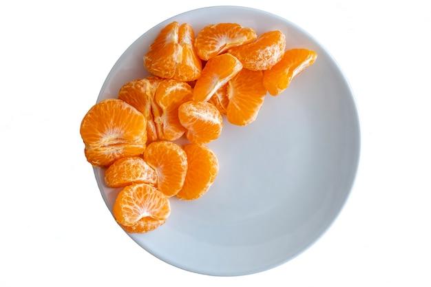 Ansicht von oben nach unten von geschälten mandarinenfrüchten auf weißem teller auf weißem hintergrund, kopierraum für text